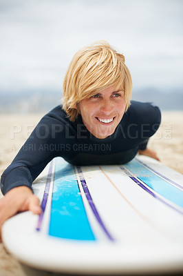 Buy stock photo Cropped shot of a female surfer lying on her surfboard