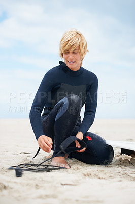 Buy stock photo Shot of a female surfer attaching her surfboard to her ankle