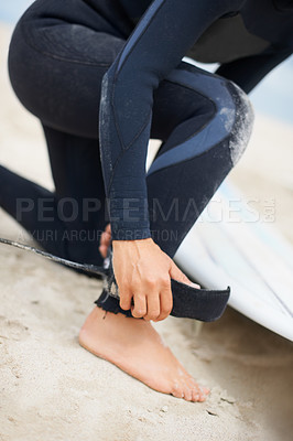 Buy stock photo Cropped shot of an unrecognizable female surfer attaching her surfboard to her ankle