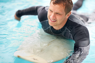 Buy stock photo Shot of a handsome young man enjoying a surf in clear blue water