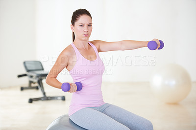 Buy stock photo Portrait of a young woman sitting on an exercise ball and doing some strengthening exercises with dumbbells
