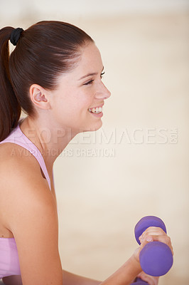 Buy stock photo Profile shot of a happy young woman lifting a dumbbell with one arm