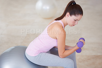 Buy stock photo Profile shot of a young woman lifting a dumbbell with one arm