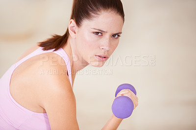 Buy stock photo Portrait of a young woman lifting a dumbbell with one arm
