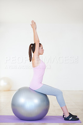 Buy stock photo Profile shot of a young woman sitting on an exercise ball and stretching her arms above her head