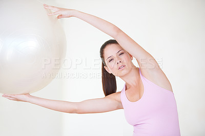 Buy stock photo Shot of a young woman with her arms stretched above her head holding an exercise ball