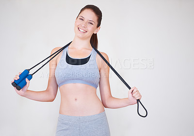 Buy stock photo Portrait of an attractive young woman holding a skipping rope over her shoulders