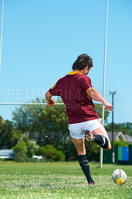 Buy stock photo Rearview shot of a rugby player kicking a ball on the rugby field