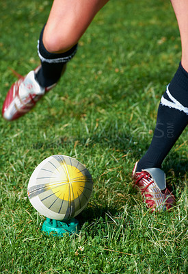 Buy stock photo Cropped shot of a rugby player kicking a ball