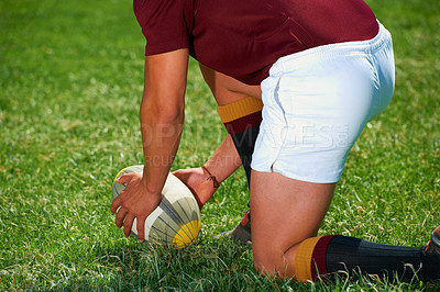 Buy stock photo Cropped shot of a rugby player setting the ball down on a rugby field