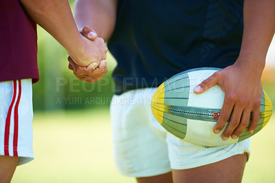 Buy stock photo Closeup shot of two rugby players from opposite teams shaking hands
