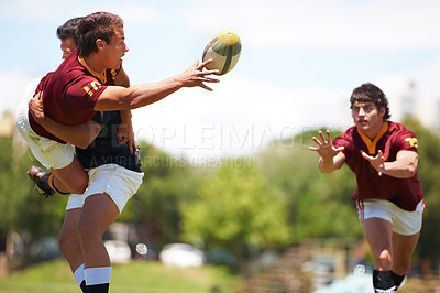 Buy stock photo Shot of a young rugby player executing a pass mid-tackle
