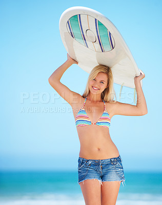 Buy stock photo A surfer girl at the beach holding up her surfboard getting ready to surf