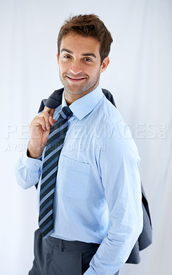 Buy stock photo Portrait of a handsome young businessman standing with his blazer hung over his shoulder and smiling