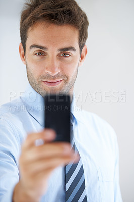 Buy stock photo A businessman holding up his phone to take a picture