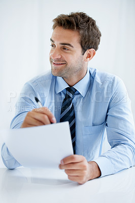 Buy stock photo A businessman sitting behind his desk and writing on a piece of paper at work