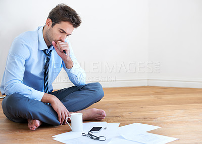 Buy stock photo A barefoot businessman sitting on the floor and looking over paperwork