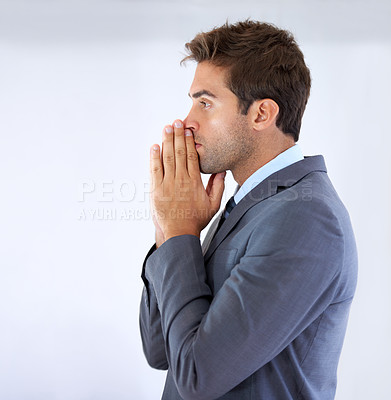 Buy stock photo Profile of a businessman standing with palms together and rested against his mouth in gesture of anticipation
