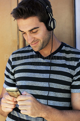 Buy stock photo A handsome young man wearing headphones and texting on his cellphone