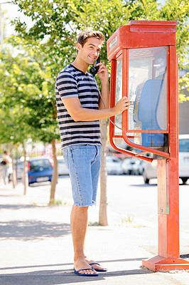 Buy stock photo Full length shot of a handsome young man smiling and having a conversation on a public telephone