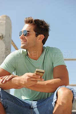 Buy stock photo Profile of a smiling handsome young man wearing sunglasses and sitting with his cellphone in hand