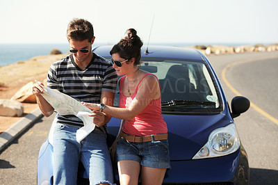 Buy stock photo A man and a woman parked on the side of the road and reading a map together while seated on the bonnet of their car