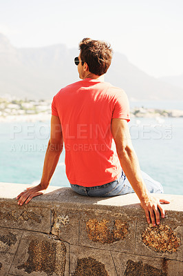 Buy stock photo Rearview of a young man sitting on a wall overlooking the sea