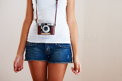 Buy stock photo Cropped image of a young woman with a vintage camera hanging around her neck