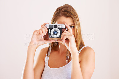 Buy stock photo A young woman holding a camera up
