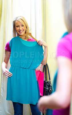 Buy stock photo A young woman checking out a dress in the changing room mirror