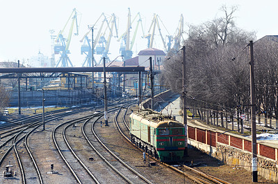 Buy stock photo Shot of a train on the tracks with industry in the background