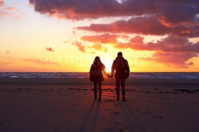 Buy stock photo Silhouette of a couple going for a walk on the beach at sunset
