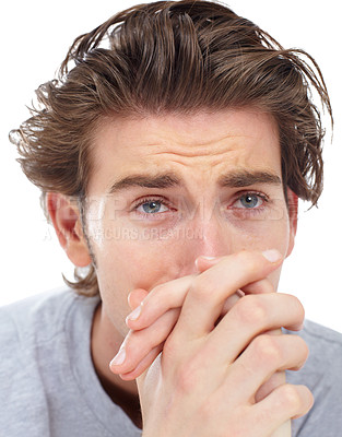 Buy stock photo Sad young man sitting with his hands clasped in front of his face