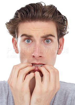 Buy stock photo Young man biting his nails and looking frightened