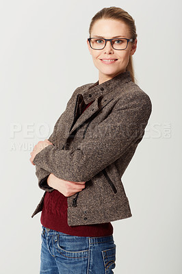 Buy stock photo Cropped studio portrait of a happy and attractive young woman standing with her arms folded