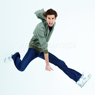 Buy stock photo Portrait of a young man jumping out and shouting loudly