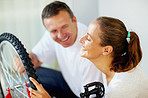 Wife laughing while husband repairing a bicycle tyre