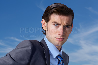Buy stock photo A confused young businessman looking at you against a blue sky
