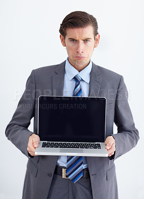 Buy stock photo A young businessman holding a laptop and grimacing