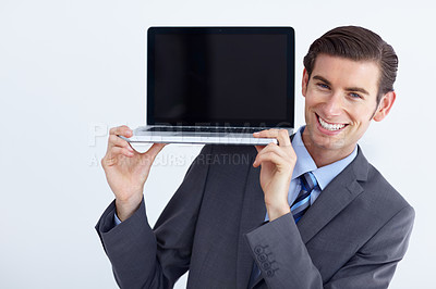 Buy stock photo A young businessman holding up a laptop and smiling
