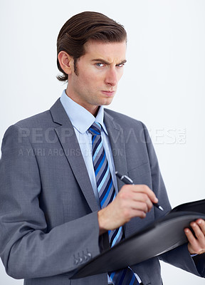 Buy stock photo A dubious businessman writing on his notepad and looking at you