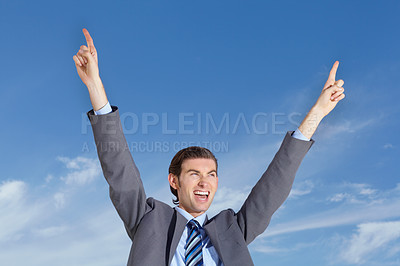 Buy stock photo A young businessman celebrating against a blue sky