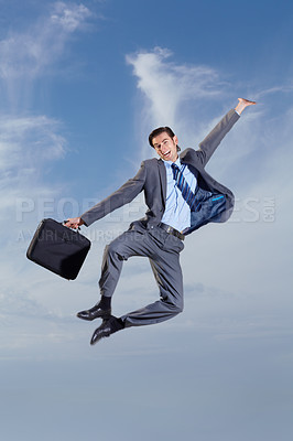 Buy stock photo A young man carrying his briefcase and leaping into the air
