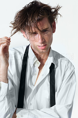 Buy stock photo A disheveled young man pulling his hair and looking at you wildly