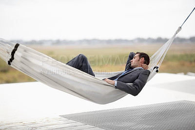 Buy stock photo A young executive in a suit taking in the landscape from a hammock