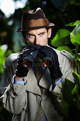 Buy stock photo Private investigator using binoculars to spy on someone from the bushes
