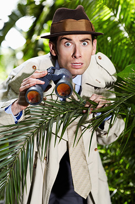 Buy stock photo Shocked private investigator using binoculars to spy on someone from the bushes