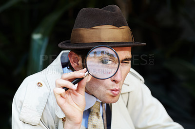 Buy stock photo Curious private investigator looking through a magnifying glass