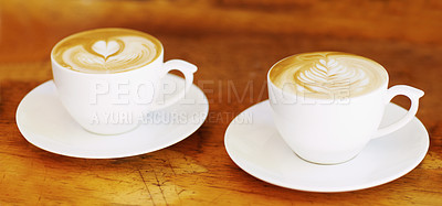 Buy stock photo Shot of two artistically prepared cups of cappuccino sitting on a table in a cafe