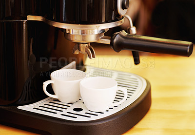 Buy stock photo Shot of two cups and an expresso making machine